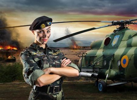 Soldaat vrouw in militair uniform staat in de buurt helikopter op het slagveld Stockfoto