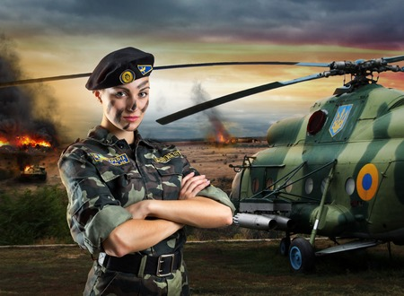 Soldier woman in military uniform is standing near helicopter on the battlefield