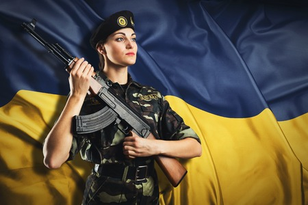 army camo: Soldier woman in uniform on the Ukraininan flag background