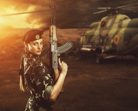 army girl: Soldier girl in military uniform is standing near helicopter on the battlefield Stock Photo