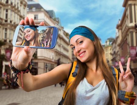take a smile: Happy traveler woman is taking selfie in a European street