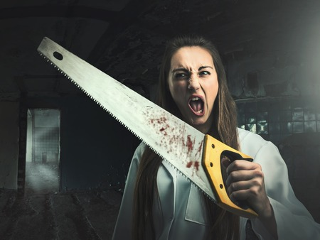 slasher: Scary portrait of an angry crazy woman with a bloody saw in her hand
