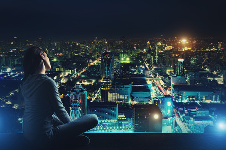 Pensive woman is sitting on the roof and looking at night city