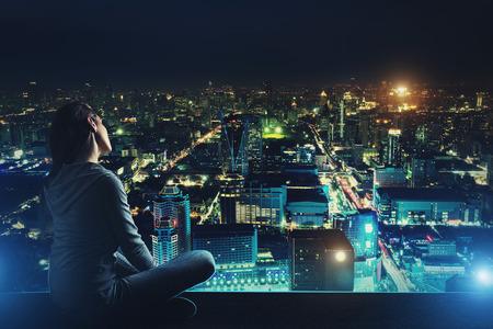 city: Mujer pensativa está sentado en el techo y mirando a la ciudad de noche