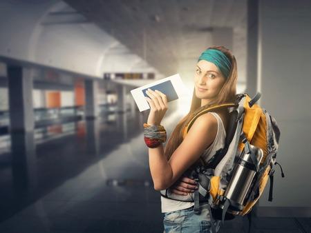 幸せな旅行者の女性は空港で彼女の飛行を待っています。 写真素材