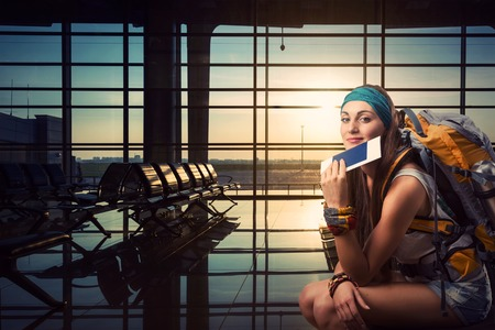 Traveler woman is waiting for her flight at the airport Foto de archivo