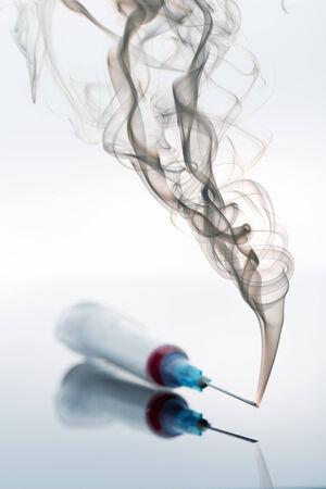 preoccupation: Syringe and smoke on white Stock Photo