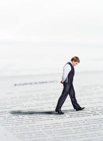 man confused: Businessman walks on papers while thinking Stock Photo