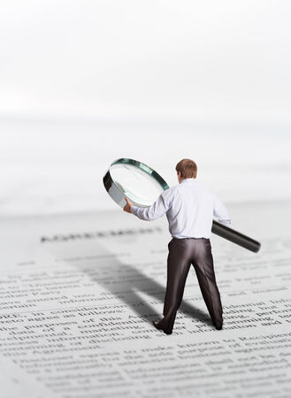 loupe: Man with big loupe stands on papers and reading an agreement Stock Photo
