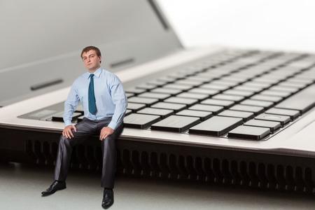 A man sitting on laptop thinks photo