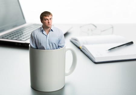 Astonished man in cup on the background of desktop photo