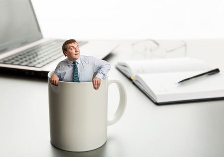Surprised man in cup on laptop background photo