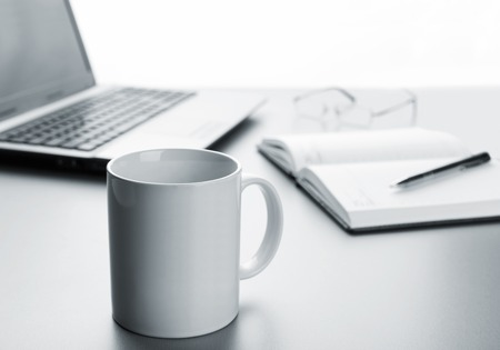 White cup, laptop, notebook and pen on the table