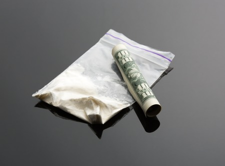 snort: Cocaine in package and one dollar bill on grey