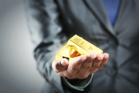 lingote oro: Cuatro barras de oro en la mano de la mujer
