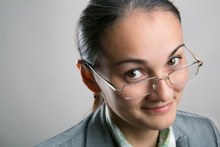 managerial: Beautiful confident female looking through her spectacles on gray background