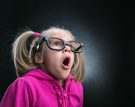 Little astonished girl in funny big spectacles on grey background