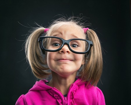 dumb: Funny little girl in big spectacles on grey