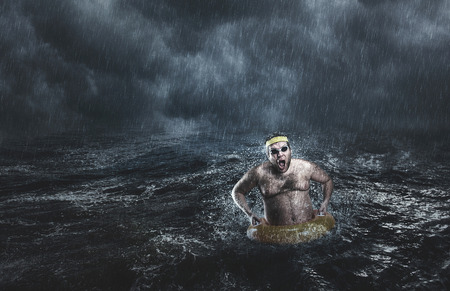 Man in the sea with lifebuoy while storming
