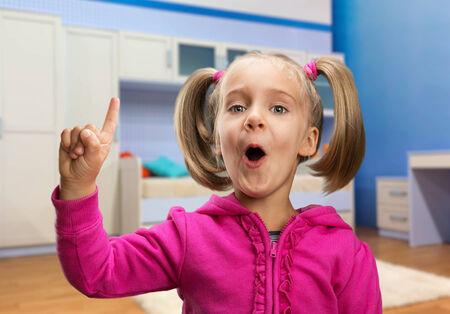 little finger: Little girl points her finger up in casual interior