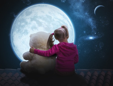 lonelyness: Small cute girl sitting with toy bear on the roof and looking at the moon Stock Photo