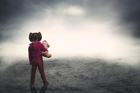 Klein meisje staande terug met speelgoed beer in de duisternis