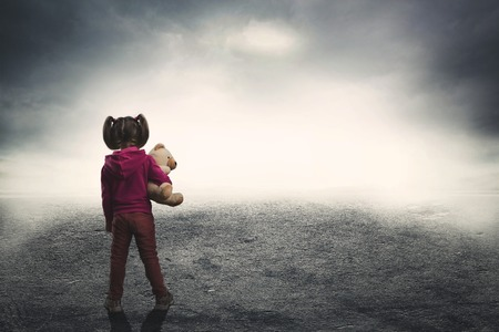 young: Little girl standing back with toy bear in the darkness Stock Photo