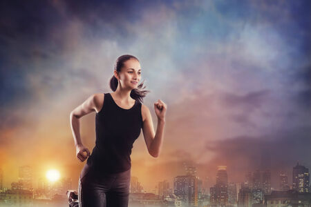 jog: Young woman running outdoors in an evening city Stock Photo