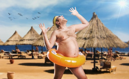 crazy: Adult man on the beach in life buoy