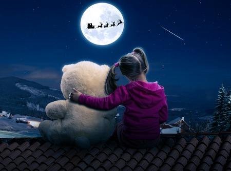 juguetes: Poco, linda chica se sienta en el techo con el oso de juguete