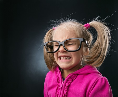 child stress: Scared little girl in funny big spectacles on grey