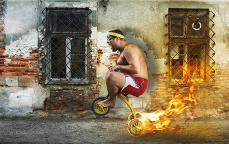 Adult crazy man cycling in the street on childs bicycle Stock Photo