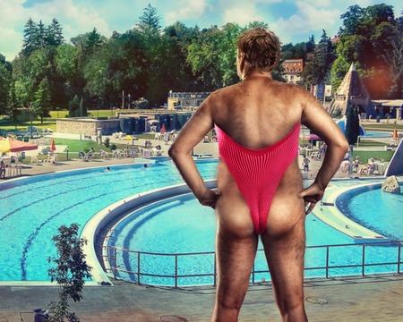 Volwassen man in de vrouw badpak staande in de buurt van het zwembad