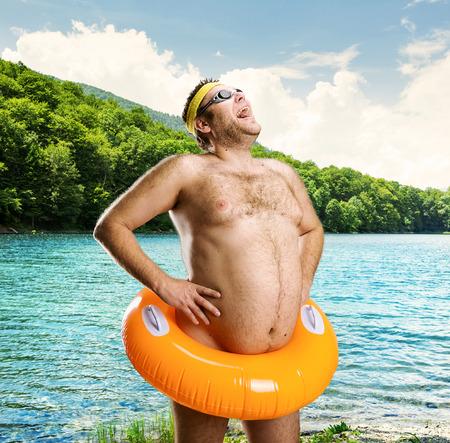 hombre desnudo: Hombre desnudo extraño con la boya de los niños en el lago Foto de archivo
