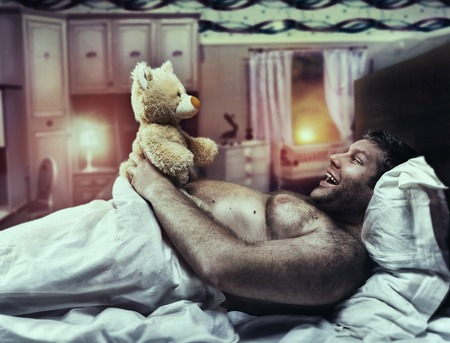 idea comfortable: Adult man at home looks at toy bear in the evening Stock Photo