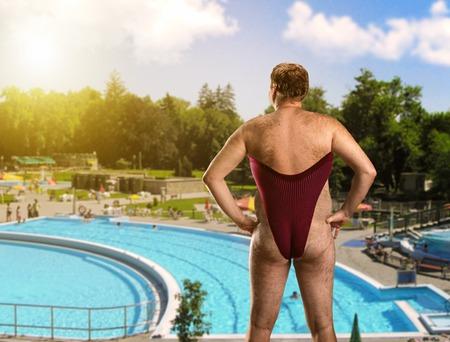 personas banandose: Hombre adulto en traje de baño de mujer se encuentra cerca de la piscina