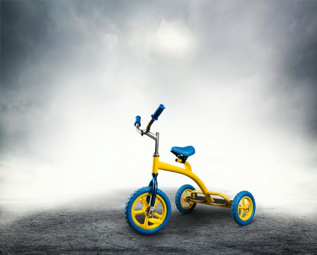 tricycle: Yellow kids bicycle stands on dark background