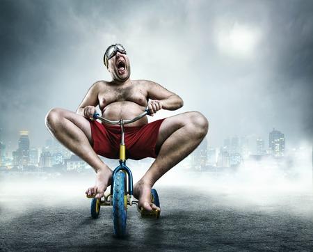 Homme adulte Nerdy monté sur un petit vélo contre la ville de fond