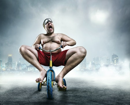 naked child: Nerdy adult man riding a small bicycle against city background