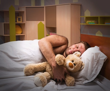 Sleeping man in bed hugs toy bear Фото со стока