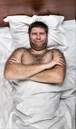 ojos cerrados: Vista superior de hombre infeliz con las manos cruzadas en la cama de blanco