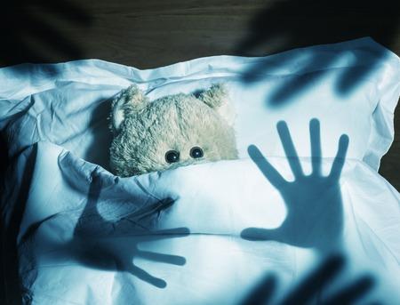 Un ours de nounours adorable pose dans son lit, effrayé par l'ombre de la main de l'homme, sous les draps.
