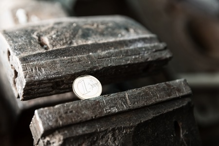 Metal bench vice with euro coin in the workshop