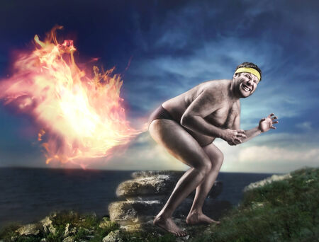 naked man: Bizarre naked man farts flame at night Stock Photo