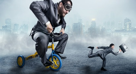nerdy: Nerdy businessman riding a small bicycle and is trying to catch a small one