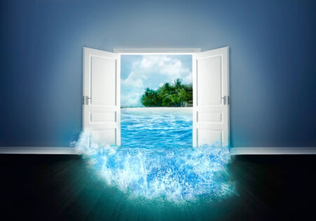 view of a wooden doorway: White wide door open to the beach Stock Photo