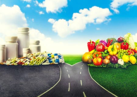 impasse: Medication decision concept and natural remedy nutrition choices dilemma between healthy fresh fruit and vegetables or pharmaceutical pills