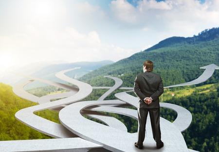 toma de decision: El hombre de negocios se destaca la elección de su camino en la naturaleza de fondo