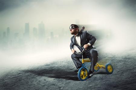 Odd businessman riding a small bicycle against dark city Archivio Fotografico