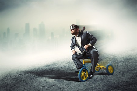 little business man: Odd businessman riding a small bicycle against dark city Stock Photo